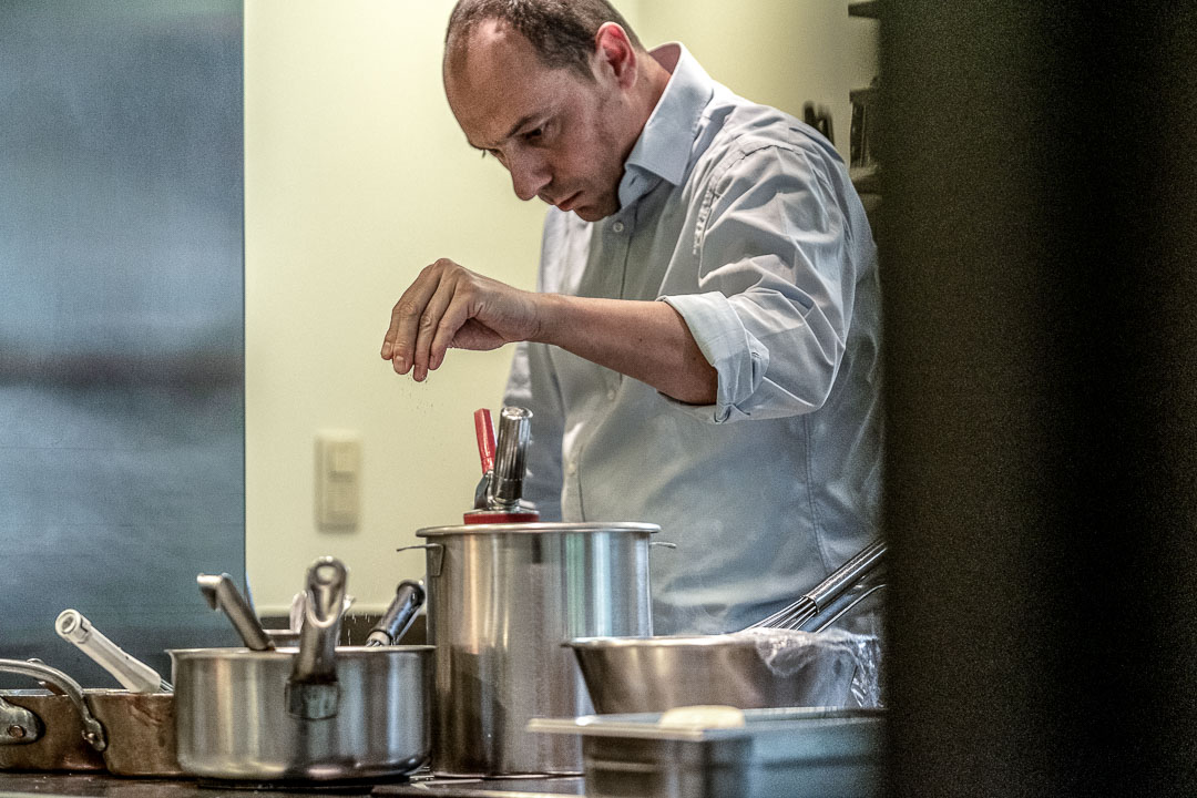Alex Hanbuckers seasoning a dish. Kitchen Action. Close-up. Auberge De Herborist by Hungry for More.