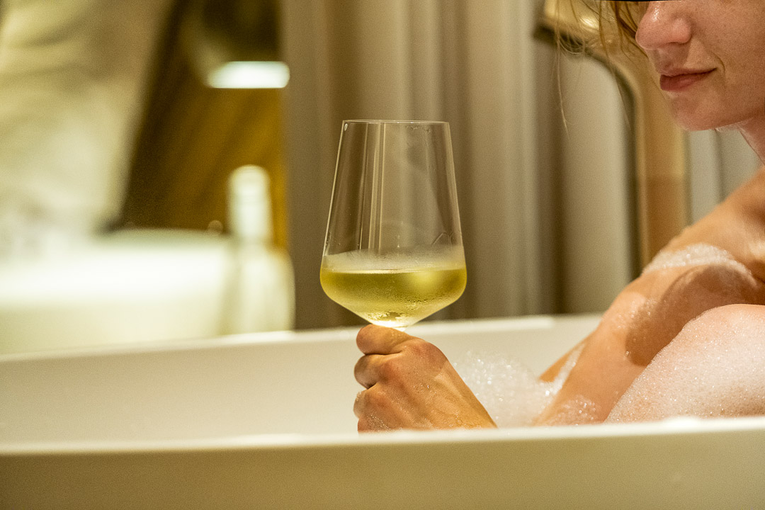 Drinking white wine in the bathtub at the Beyond hotel in Munich.