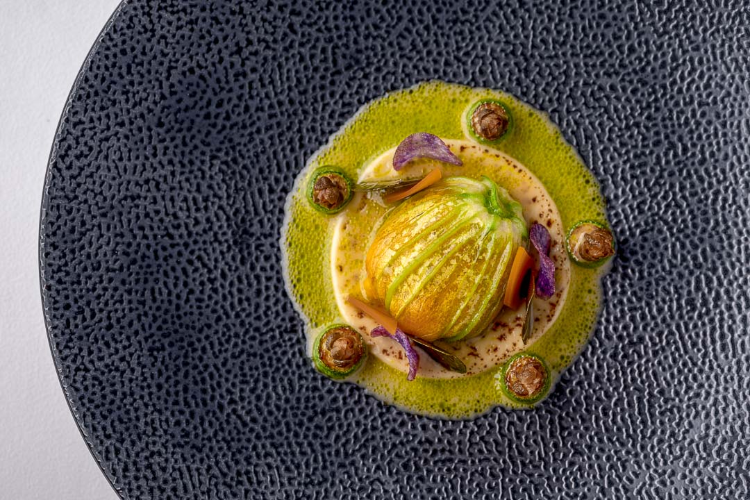 Burg Schwarzenstein and Nils Henkel by Hungry for More. Flora Menu. Courgette blossom, smoked potato, mimolette and capers. Top view.