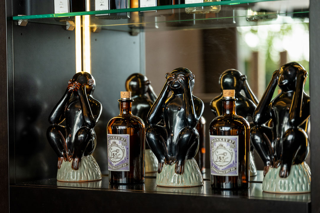 Burg Schwarzenstein and Nils Henkel by Hungry for More. Restaurant. Bottles and 3 decorative monkeys in a cabinet.