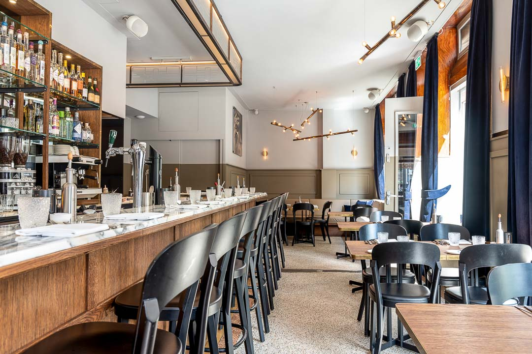 Interior with tables, chairs and lighting and bar at Restaurant Daalder in Amsterdam.