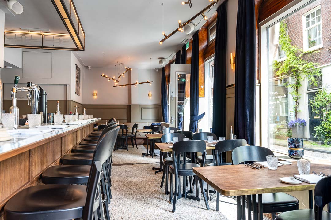 Interior with tables, chairs and lighting and bar at Restaurant Daalder in Amsterdam