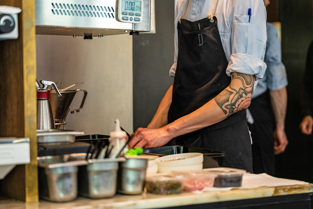 Male staff with elbow tattoo preparing food in the kitchen at Restaurant Daalder in Amsterdam.