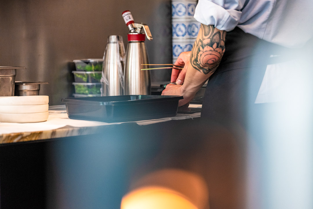 Male staff with elbow tattoo preparing food with tweezers n the kitchen at Restaurant Daalder in Amsterdam.