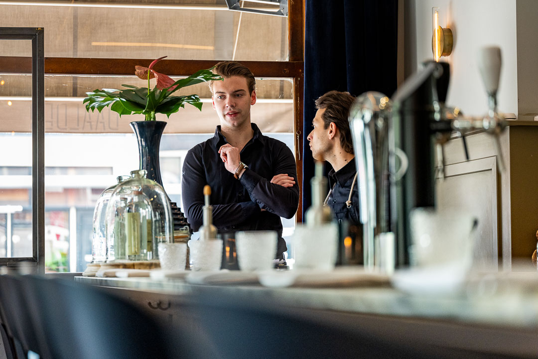 Male staff consulting behind the bar at Restaurant Daalder in Amsterdam.