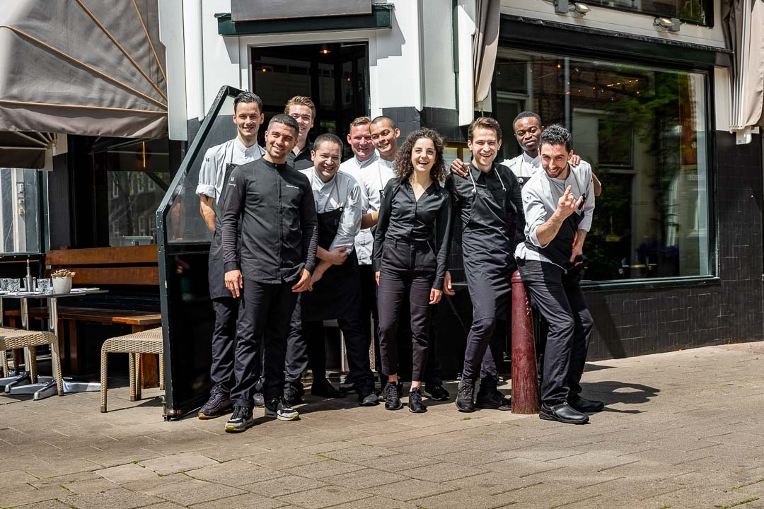 Group photo of the Daalder-team posing in front of Restaurant Daalder in Amsterdam