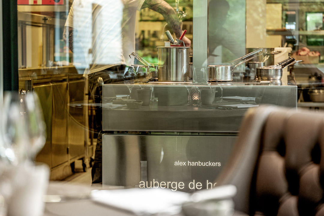 Kitchen Action. Male staff with tattoo stirring pots behind a glass window. Close-up. Auberge De Herborist by Hungry for More.