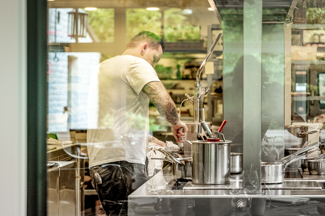 Kitchen Action. Male staff with tattoo behind a glass window. Auberge De Herborist by Hungry for More.