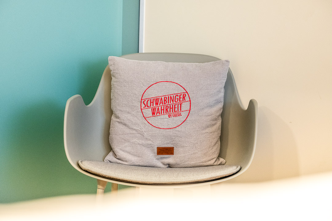 Schwabinger Wahrheit Munich by Geisel by Hungry for More. Chair with a pillow with logo.