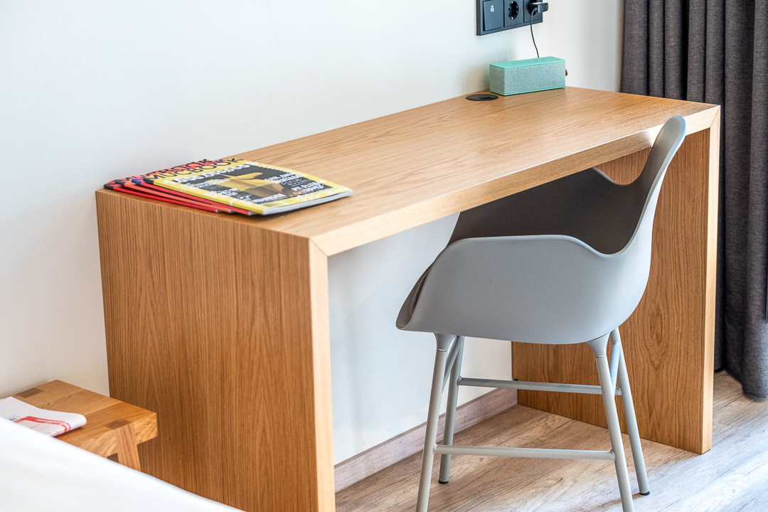 Schwabinger Wahrheit Munich by Geisel by Hungry for More. Desk with magazines and a chair.