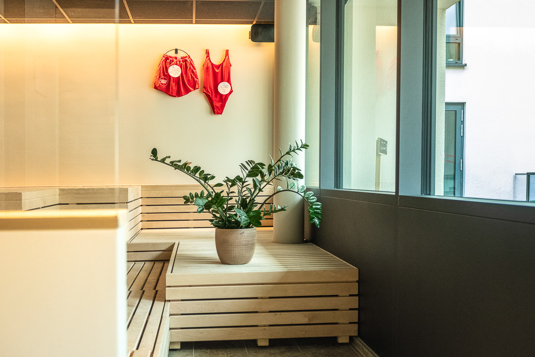 Schwabinger Wahrheit Munich by Geisel by Hungry for More. Spa. Red swimsuits on a wall and a plant.