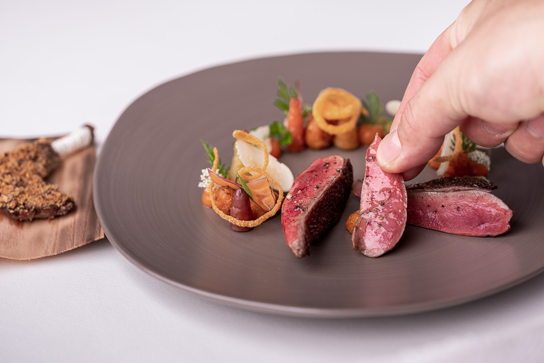 Werneckhof Munich by Hungry for More. Anjou Pigeon, carrot, pecan nut, passion fruit & curry leaves. Front action view 1.
