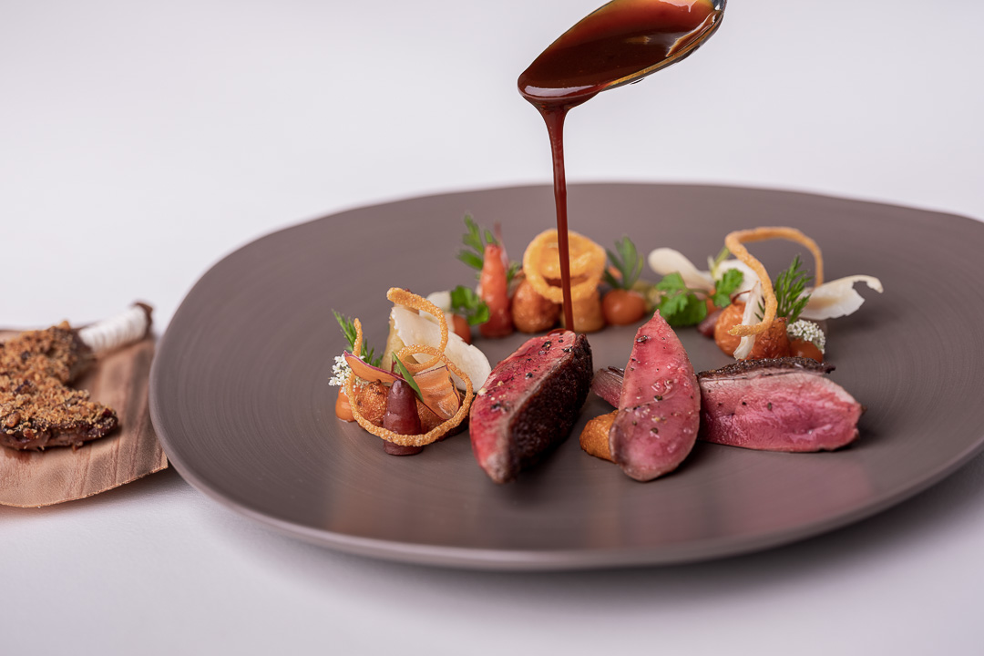 Werneckhof Munich by Hungry for More. Anjou Pigeon, carrot, pecan nut, passion fruit & curry leaves. Front action view 2.