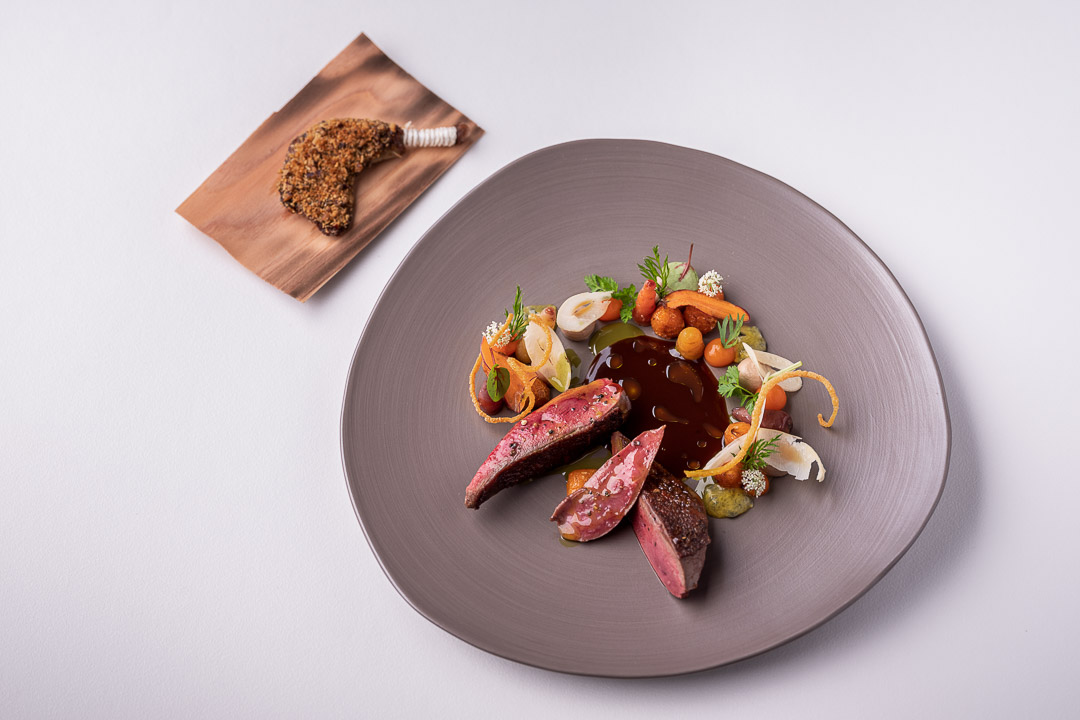 Werneckhof Munich by Hungry for More. Anjou Pigeon, carrot, pecan nut, passion fruit & curry leaves. Top view.