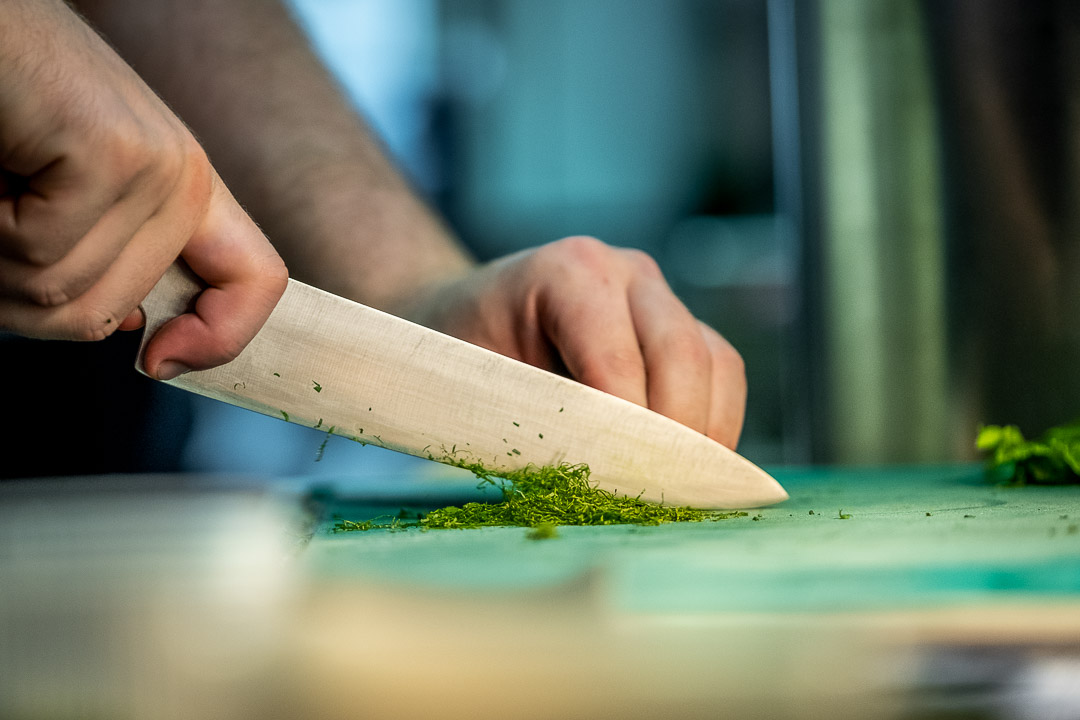 Werneckhof Munich by Hungry for More. Kitchen staff member cutting herbs with a knife.