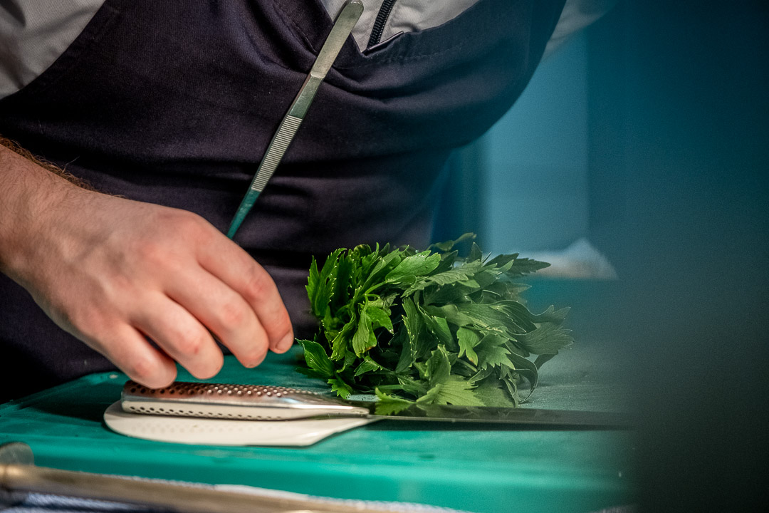 Werneckhof Munich by Hungry for More. Kitchen staff ready to cut herbs with a knife.