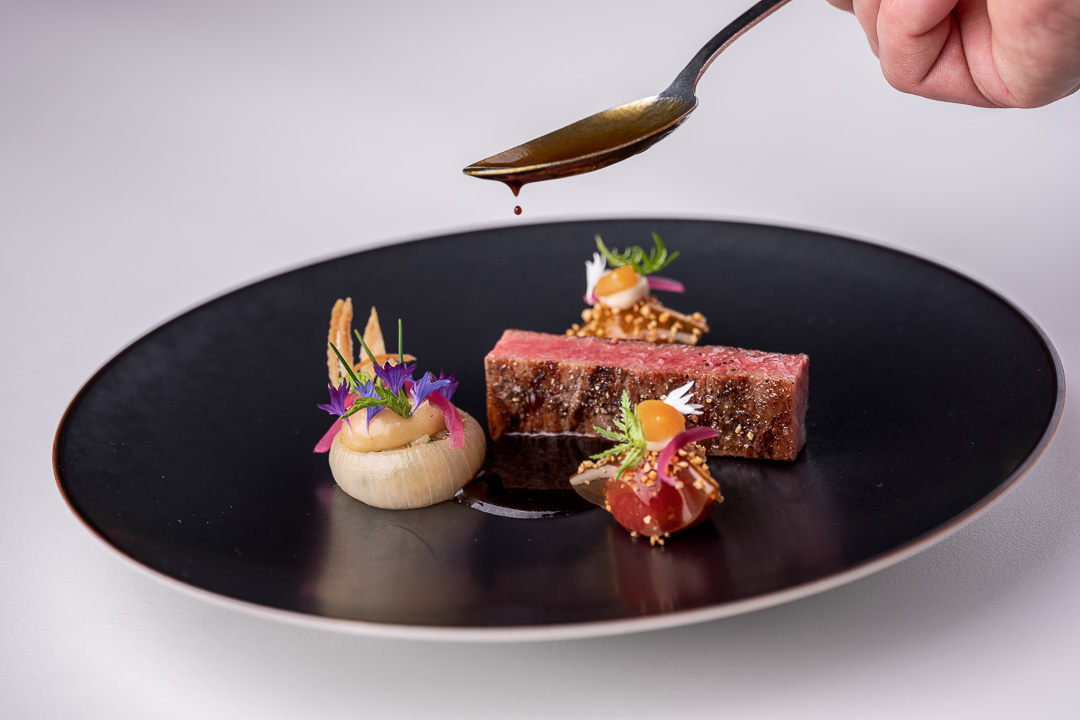 Werneckhof Munich by Hungry for More. Ozaki Wagyu, soy infused cherry tomato, stuffed onions, Shiokoji & basil. Front action view 1.