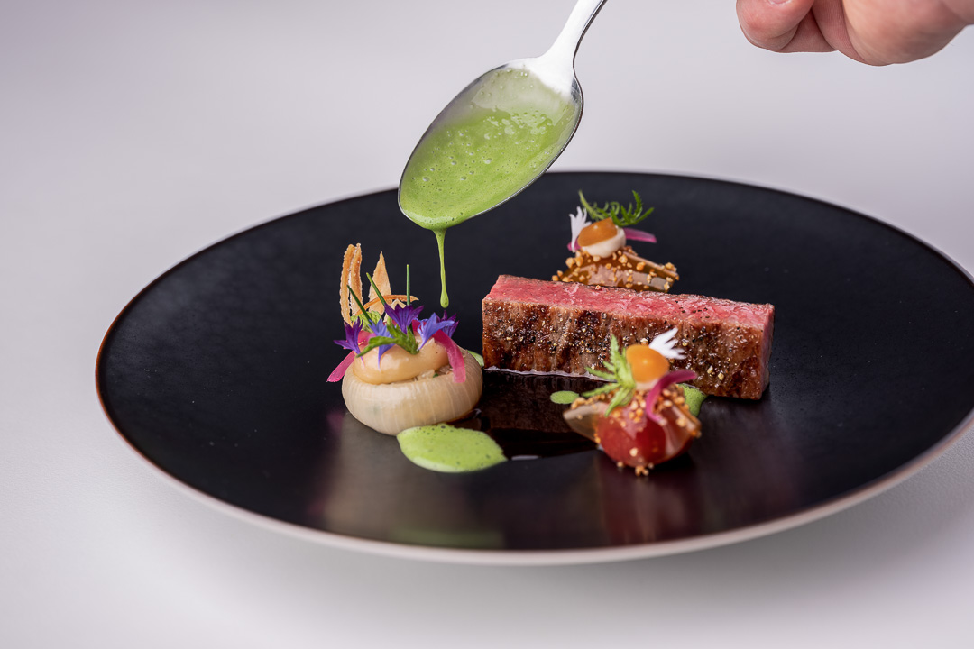 Werneckhof Munich by Hungry for More. Ozaki Wagyu, soy infused cherry tomato, stuffed onions, Shiokoji & basil. Front action view 2.