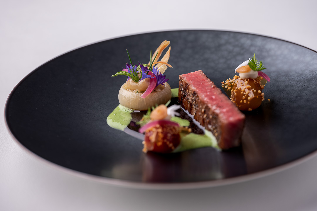 Werneckhof Munich by Hungry for More. Ozaki Wagyu, soy infused cherry tomato, stuffed onions, Shiokoji & basil. Front view.