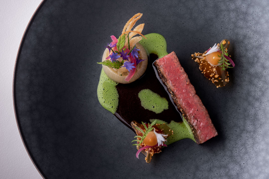 Werneckhof Munich by Hungry for More. Ozaki Wagyu, soy infused cherry tomato, stuffed onions, Shiokoji & basil. Top view.