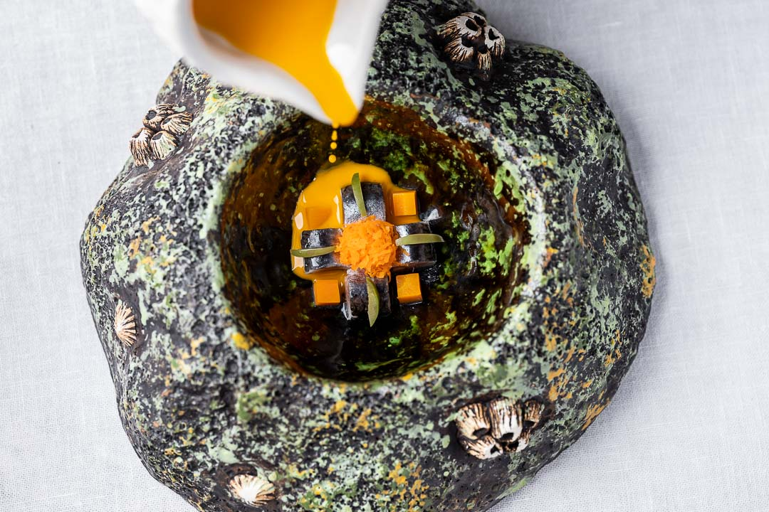 Aponiente by Hungry for More. Carrot and cumin gazpacho with different textures, anchovies and olive. Top action view.
