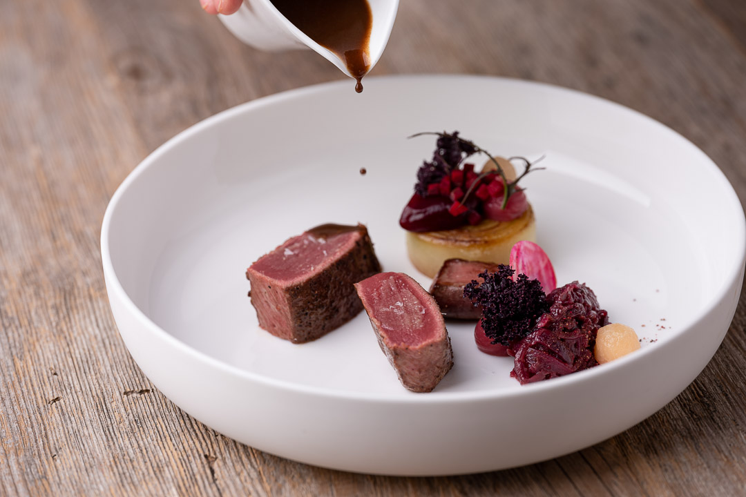 L'Envie by Hungry for More. Chef David Grosdent pouring the sauce on the roe deer dish.